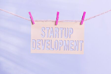 Word writing text Startup Development. Business photo showcasing developing idea which signifying birth of the business Clothesline clothespin rectangle shaped paper reminder white wood desk