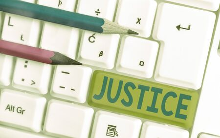 Conceptual hand writing showing Justice. Concept meaning use of power as appointed by law standards to support fair treatment White pc keyboard with empty note paper above white key copy space