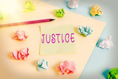 Word writing text Justice. Business photo showcasing use of power as appointed by law standards to support fair treatment Colored crumpled papers empty reminder blue yellow background clothespin