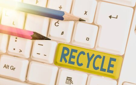 Conceptual hand writing showing Recycle. Concept meaning process of converting waste materials into new materials and objects White pc keyboard with empty note paper above white key copy space Reklamní fotografie