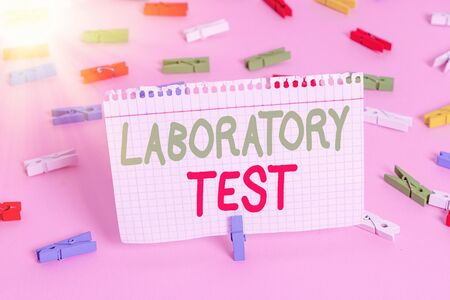 Handwriting text Laboratory Test. Conceptual photo Determination of a medical diagnosis from the substances tested Colored clothespin papers empty reminder pink floor background office pin 스톡 콘텐츠