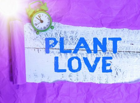 Writing note showing Plant Love. Business concept for a symbol of emotional love, care and support showed to others Rolled ripped torn cardboard above a wooden classic table