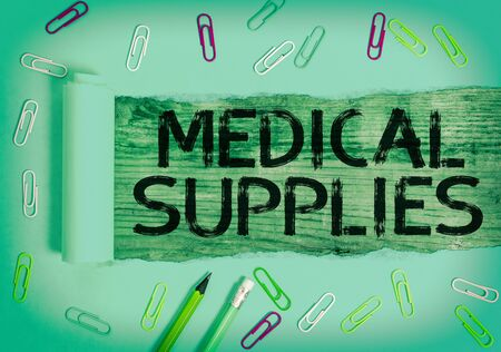 Conceptual hand writing showing Medical Supplies. Concept meaning Items necessary for treatment of illness or injury Rolled ripped torn cardboard above a wooden classic table