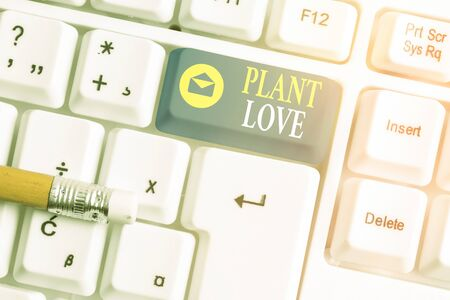 Writing note showing Plant Love. Business concept for a symbol of emotional love, care and support showed to others White pc keyboard with empty note paper above white key copy space