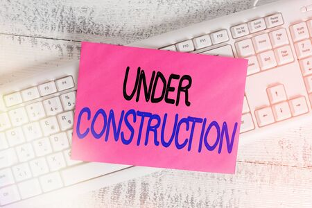 Word writing text Under Construction. Business photo showcasing building that is unfinished but actively being worked on White keyboard office supplies empty rectangle shaped paper reminder wood