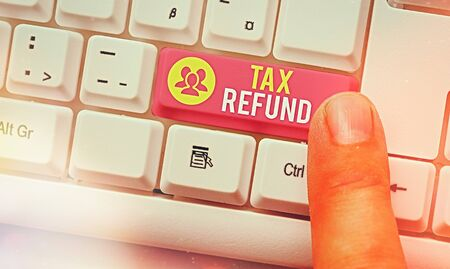 Word writing text Tax Refund. Business photo showcasing excess payment of paid taxes returned to business owners White pc keyboard with empty note paper above white key copy space Foto de archivo