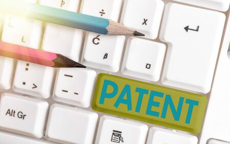 Conceptual hand writing showing Patent. Concept meaning intellectualproperty that gives owner legal right has the sole right White pc keyboard with empty note paper above white key copy space Foto de archivo - 150247293