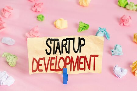 Writing note showing Startup Development. Business concept for developing idea which signifying birth of the business Colored crumpled papers empty reminder pink floor background clothespin