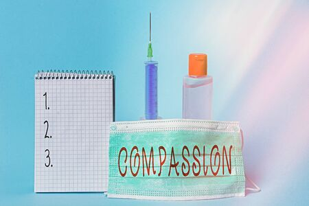 Conceptual hand writing showing Compassion. Concept meaning empathy and concern for the pain or misfortune of others Set of medical equipment with notepad for health assessment