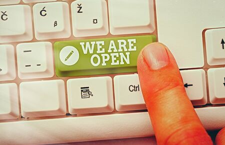 Handwriting text We Are Open. Conceptual photo no enclosing or confining barrier, accessible on all sides White pc keyboard with empty note paper above white key copy space