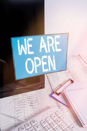 Writing note showing We Are Open. Business concept for no enclosing or confining barrier, accessible on all sides Note paper taped to black computer screen near keyboard and stationary