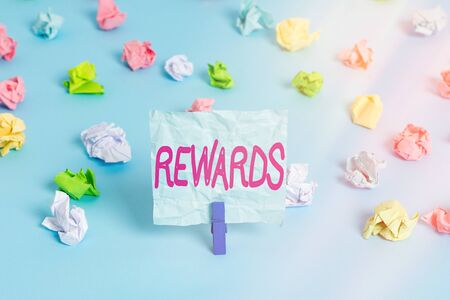 Handwriting text Rewards. Conceptual photo certain number or percentage you earn for every dollar you charge Colored crumpled papers empty reminder blue floor background clothespin