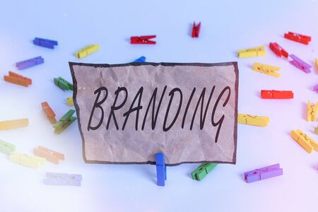 Word writing text Branding. Business photo showcasing promotion of product by means of advertising and distinctive design Colored clothespin papers empty reminder white floor background office