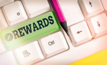 Writing note showing Rewards. Business concept for certain number or percentage you earn for every dollar you charge