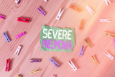 Conceptual hand writing showing Severe Pneumonia. Concept meaning acute disease that is marked by inflammation of lung tissue Colored crumpled papers wooden floor background clothespin Standard-Bild