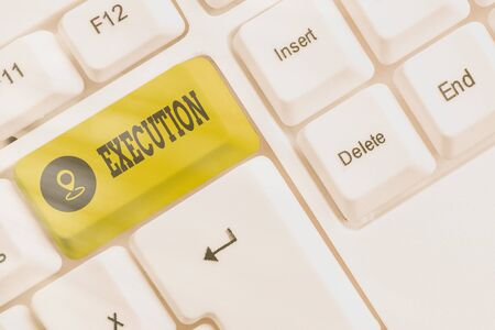 Writing note showing Execution. Business concept for it executes or imposes a program order or course of action White pc keyboard with empty note paper above white key copy space Zdjęcie Seryjne