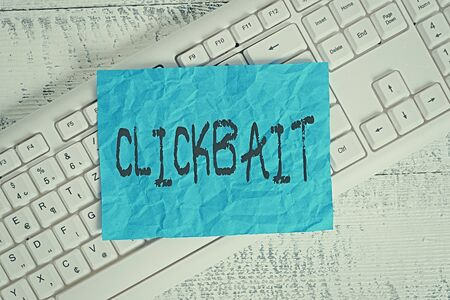 Text sign showing Clickbait. Business photo text the main purpose is to attract attention to a particular web page White keyboard office supplies empty rectangle shaped paper reminder wood