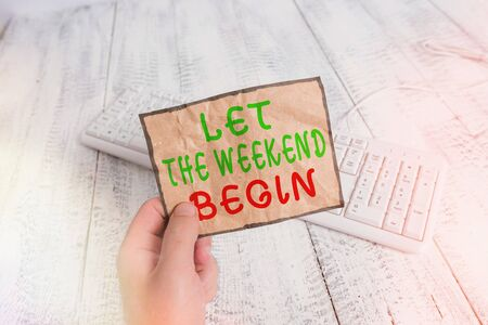 Conceptual hand writing showing Let The Weekend Begin. Concept meaning happy Saturday Welcome Holiday Lets enjoy the day Man holding colorful reminder square shaped paper wood floor