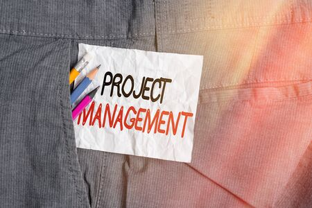 Text sign showing Project Management. Business photo showcasing practice of the work of a team to achieve specific goals Writing equipment and white note paper inside pocket of man work trousers