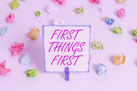 Conceptual hand writing showing First Things First. Concept meaning Business, technology, internet, set your priorities and most important Colored crumpled paper empty reminder white floor clothespin Zdjęcie Seryjne