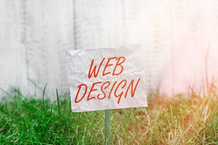 Conceptual hand writing showing Web Design. Concept meaning website creation which includes layout, content, and graphics Plain paper attached to stick and placed in the grassy land