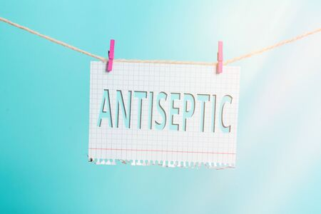 Text sign showing Antiseptic. Business photo text antimicrobial agents that delays or completely eliminate the microorganism Clothesline clothespin rectangle shaped paper reminder white wood desk