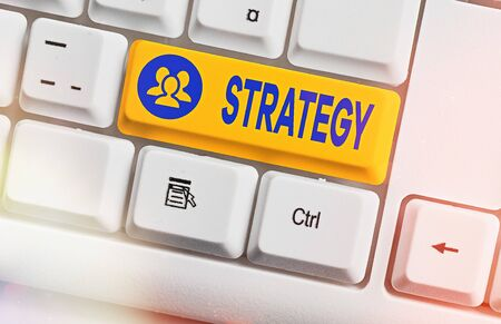 Conceptual hand writing showing Strategy. Concept meaning action plan or strategy designed to achieve an overall goal White pc keyboard with empty note paper above white key copy space Foto de archivo