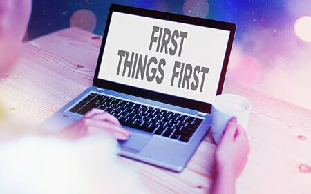 Conceptual hand writing showing First Things First. Concept meaning Business, technology, internet, set your priorities and most important Modern gadgets white screen under colorful bokeh background