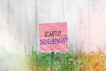 Conceptual hand writing showing Startup Development. Concept meaning developing idea which signifying birth of the business Plain paper attached to stick and placed in the grassy land