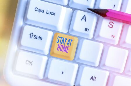 Writing note showing Stay At Home. Business concept for movement control restricting individuals from getting exposed publicly White pc keyboard with empty note paper above white key copy space Stock Photo