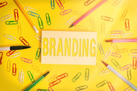 Conceptual hand writing showing Branding. Concept meaning promotion of product by means of advertising and distinctive design Flat lay above empty paper with pencils and paper clips 版權商用圖片