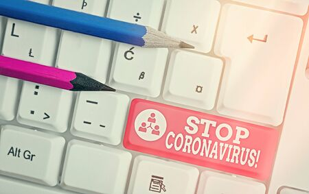 Text sign showing Stop Coronavirus. Business photo showcasing Disease awareness campaign fighting to lessen the COVID19 cases White pc keyboard with empty note paper above white key copy space