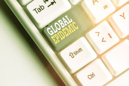 Conceptual hand writing showing Global Epidemic. Concept meaning a rapid spread of a communicable disease over a wide geographic area White pc keyboard with note paper above white key copy space