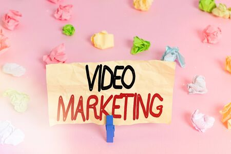 Writing note showing Video Marketing. Business concept for using videos to promote and market your product or service Colored crumpled papers empty reminder pink floor background clothespin