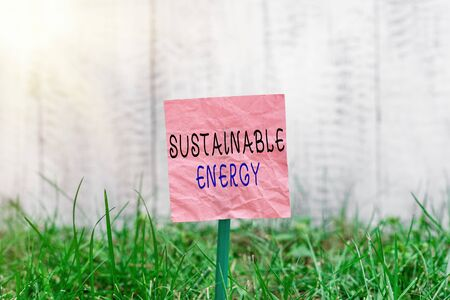 Conceptual hand writing showing Sustainable Energy. Concept meaning practice of using energy that meets the needs of present Plain paper attached to stick and placed in the grassy land