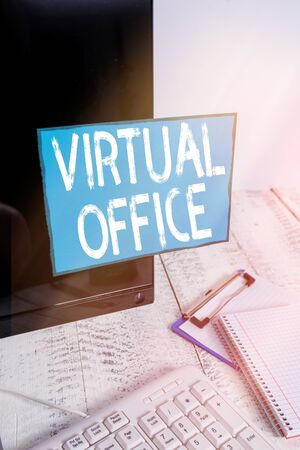 Writing note showing Virtual Office. Business concept for operational domain of any business or organization virtually Note paper taped to black computer screen near keyboard and stationary