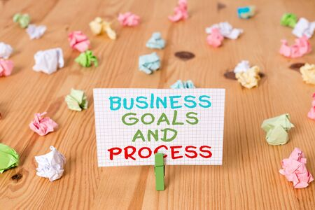 Conceptual hand writing showing Business Goals And Process. Concept meaning company planning and strategies to accomplish Colored crumpled papers wooden floor background clothespin