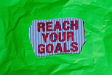 Conceptual hand writing showing Reach Your Goals. Concept meaning Business and success, Focus with determination to build your future Green crumpled colored paper sheet torn colorful background