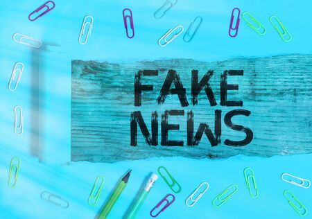 Conceptual hand writing showing Fake News. Concept meaning false information publish under the guise of being authentic news Rolled ripped torn cardboard above a wooden classic table