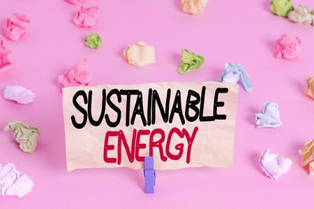 Writing note showing Sustainable Energy. Business concept for practice of using energy that meets the needs of present Colored crumpled papers empty reminder pink floor background clothespin Standard-Bild