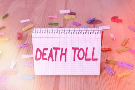 Handwriting text writing Death Toll. Conceptual photo the number of deaths resulting from a particular incident Colored clothespin papers empty reminder wooden floor background office
