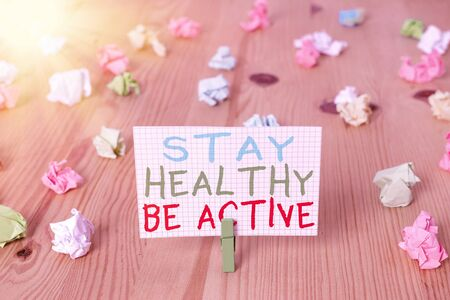 Conceptual hand writing showing Stay Healthy Be Active. Concept meaning physical activity and having energy and strength Colored crumpled papers wooden floor background clothespin