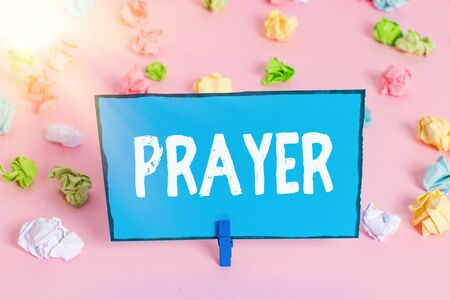 Writing note showing Prayer. Business concept for solemn request for help or expression of thanks addressed to God Colored crumpled papers empty reminder pink floor background clothespin