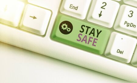 Writing note showing Stay Safe. Business concept for secure from threat of danger, harm or place to keep articles White pc keyboard with empty note paper above white key copy space