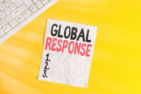 Text sign showing Global Response. Business photo showcasing indicates the behaviour of material away from impact point Copy space on notebook above yellow background with pc keyboard on the table