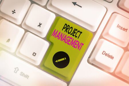 Conceptual hand writing showing Project Management. Concept meaning practice of the work of a team to achieve specific goals White pc keyboard with empty note paper above white key copy space