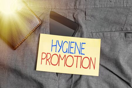 Word writing text Hygiene Promotion. Business photo showcasing systematic program to prevent related disease with sanitation Smartphone device inside trousers front pocket with wallet and note paper Stock Photo