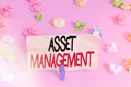Writing note showing Asset Management. Business concept for precise handling of resources for future economic benefits Colored crumpled papers empty reminder pink floor background clothespin