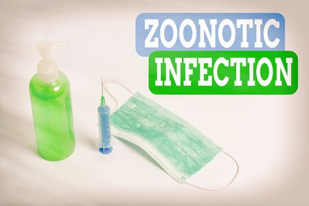 Writing note showing Zoonotic Infection. Business concept for communicable disease transmitted by a non viral agent Primary medical precautionary equipments for health care protection