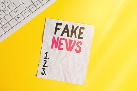 Text sign showing Fake News. Business photo showcasing false information publish under the guise of being authentic news Copy space on notebook above yellow background with pc keyboard on the table Stock Photo
